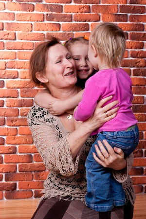 Grandmother playing with her grandchildren against brick wall photo