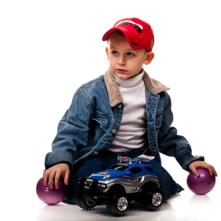 Cute little boy playing with car isolated on white photo