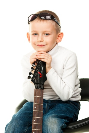 Cute little boy holding a guitar isolated on white photo