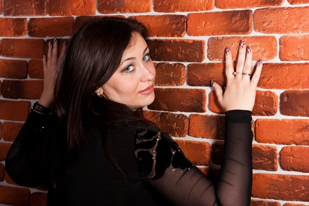 Beautiful woman leaning against brick wall smiling photo