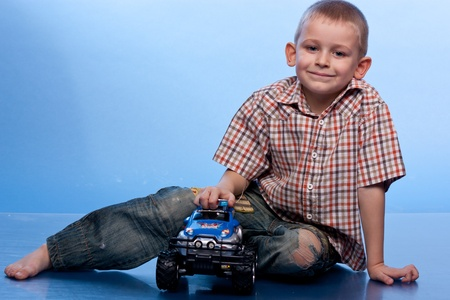 Happy boy playing with car against blue brackground photo