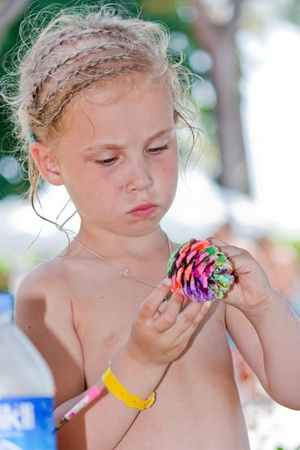 little girl beach: Beautiful baby girl painting pine cone outdoor Stock Photo