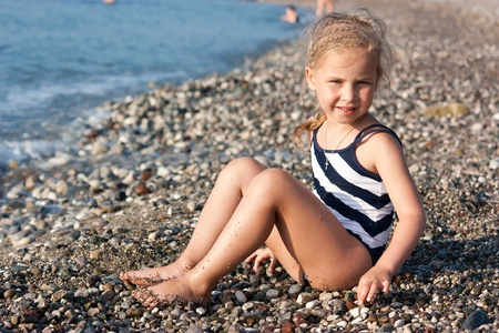 Beautiful girl sitting on the beach at the seashore photo
