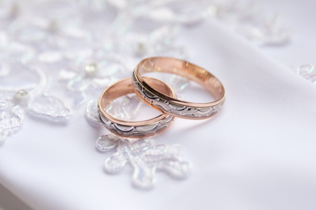 shallow dof: Pair of wedding rings on white gloves in the background. Very shallow DOF