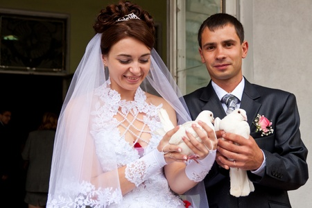 Happy groom and bride holding wedding pigeons in hands Stock Photo - 10272091