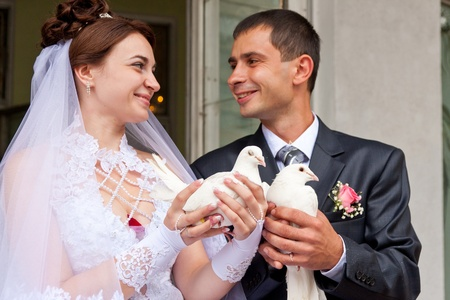 releasing: Happy groom and bride holding wedding pigeons in hands Stock Photo