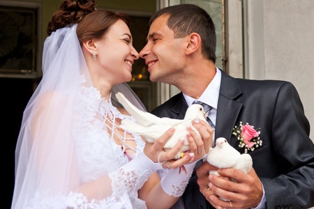 Happy groom and bride holding wedding pigeons in hands Stock Photo - 10272092