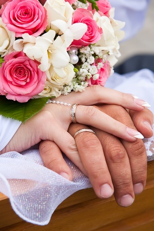 Ruce ženicha a nevěsty a kroužky s svatební kytice