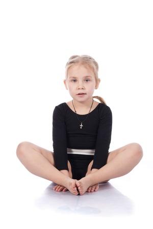 Niña gimnasta sentado en pose de mariposa aislado en blanco