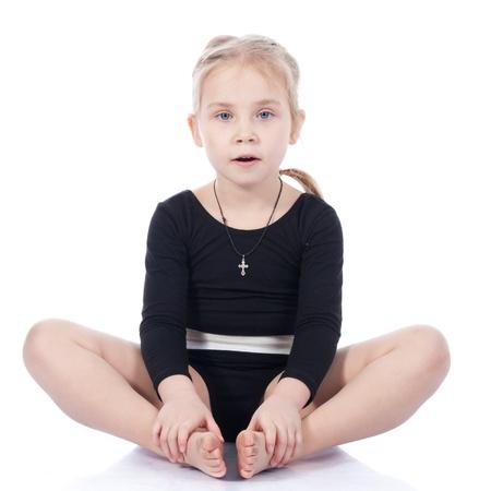 Gymnastka dívka sedící v motýla představovat izolovaných na bílém