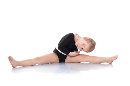 Studio portrait of girl gymnasts, sitting on the splits, isolation on white.