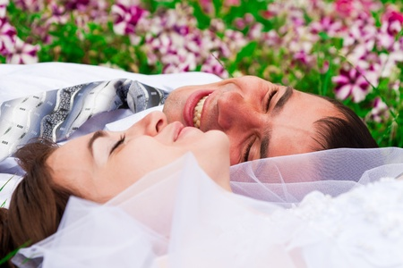 Happy smiling bride and groom  lying on a green grass laughing photo