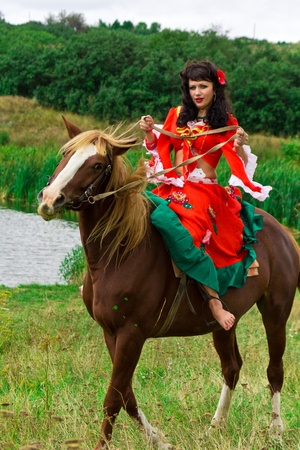 Beautiful gypsy girl riding a horse in the field Фото со стока