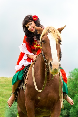 gipsy: Beautiful gypsy girl riding a horse in the field Stock Photo