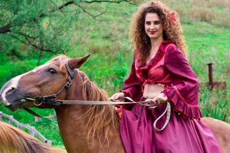 Beautiful gypsy girl riding a horse in the field Reklamní fotografie