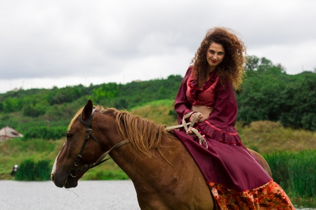 Beautiful gypsy girl riding a horse in the field Stock Photo - 10421595