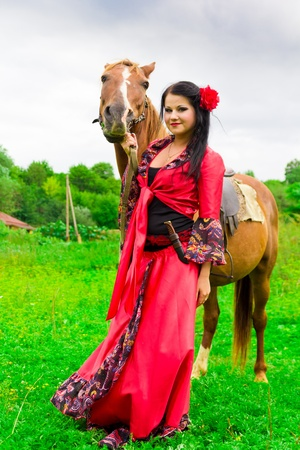 Beautiful gypsy girl with a horse in the field photo