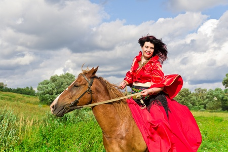 Beautiful gypsy girl riding a horse in the field Stock Photo - 10448418