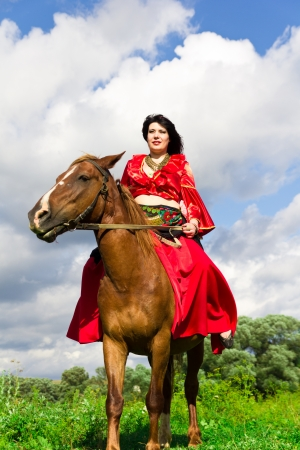 fancy dress costume: Beautiful gypsy girl riding a horse in the field Stock Photo