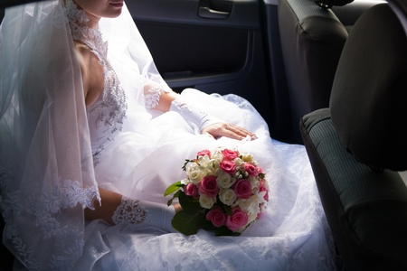 Beautiful bride sitting in the car alone photo