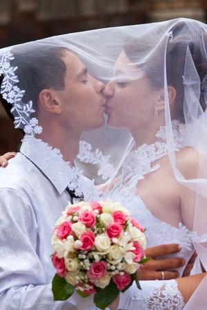 Bride and groom kissing under the veil photo