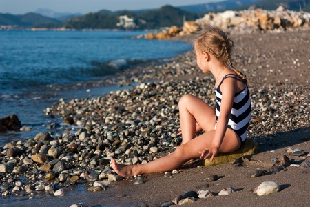 waves  pebble: Beautiful girl sitting on a beach at the seashore Stock Photo