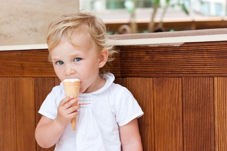 Cute child eating icecream outdoor
