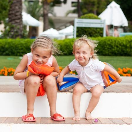 Roztomilé dívky připravují jít plavat v páskami na rukávech ve středisku