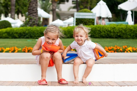 armbands: Cute girls preparing to go to swim in armbands in the resort Stock Photo