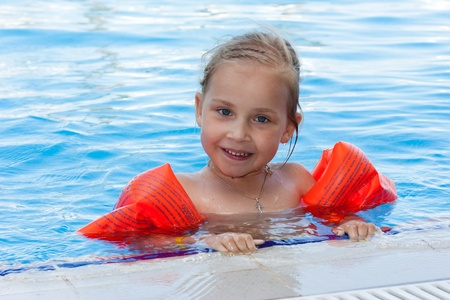 armbands: Adorable girl in armbands in swimming pool outdoor