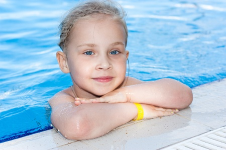 Adorable girl in armbands in swimming pool outdoor photo