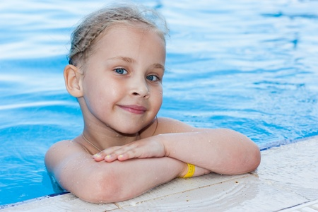 Adorable girl in swimming pool outdoor