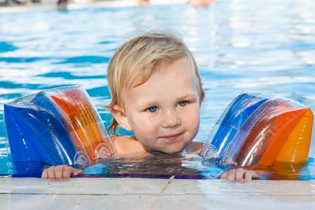 Roztomilá holčička v páskami na rukávech v bazén venkovní Reklamní fotografie