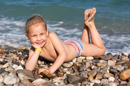 little girl swimsuit: Beautiful girl lying at the seashore in waves and splashes