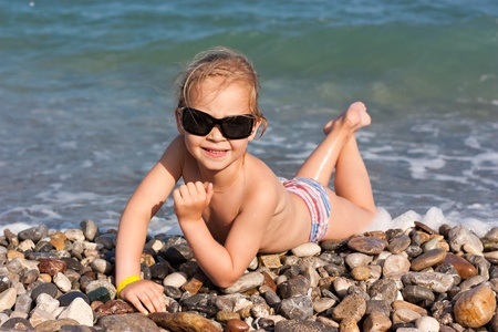 beach blond hair: Beautiful girl lying at the seashore in waves and splashes