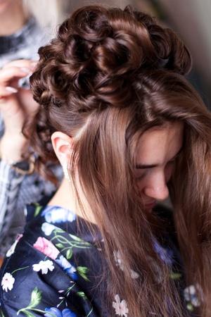 Handen van de kapper doen van haar om de bruid