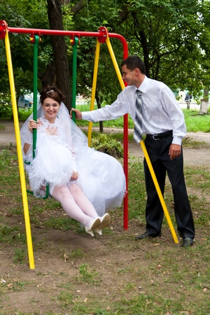 Bride sitting on swings and groom standing near outdoor photo