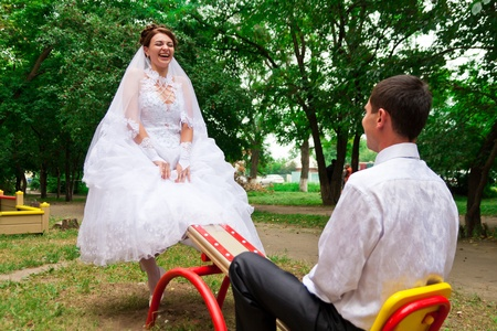 Bride and groom on a seesaw on children photo