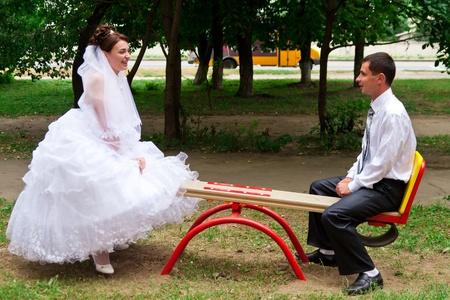 La novia y el novio en un sube y baja en los niños