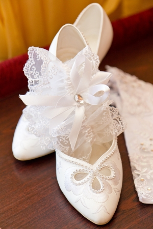 Brides shoes and garter on wooden table photo