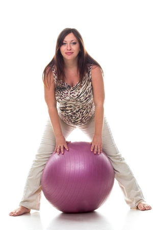 Pregnant woman excercises with gymnastic ball isolated on white