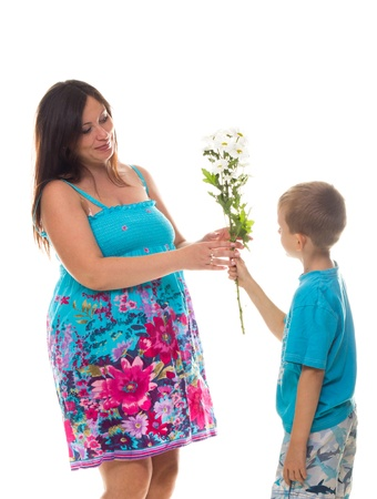 Son giving flowers to his pregnant mother isolated on white