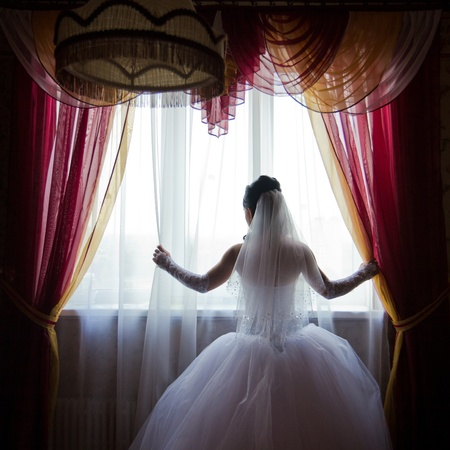 Silhouette of a beautiful bride in wedding dress standing by the window.  photo