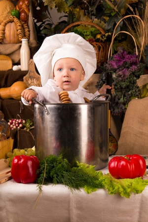 Portrait of a baby wearing a chef hat sitting inside a large cooking stock pot surrounded by vegetables and food