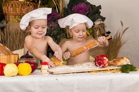 Kids dressed as chefs cooking surrounded with food photo