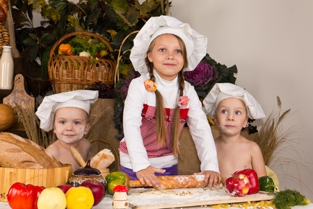 Kids dressed as chefs cooking surrounded with food Reklamní fotografie