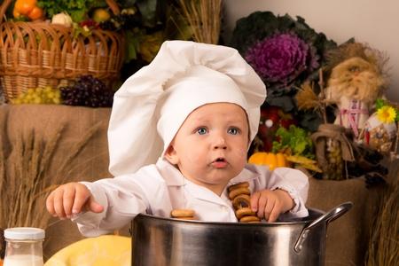 Portrét dítě na sobě kuchař klobouk seděl uvnitř velké vaření akciové hrnec obklopené zeleniny a potravin