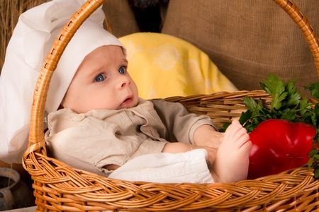 little boy in the cook costume in a basket at the kitchen  Reklamní fotografie