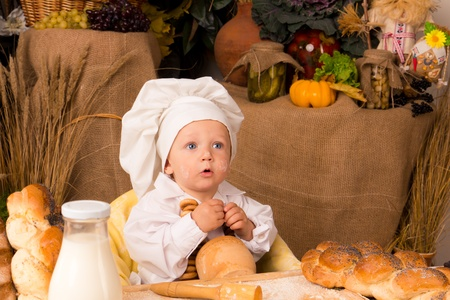 little boy in the cook costume at the kitchen  photo