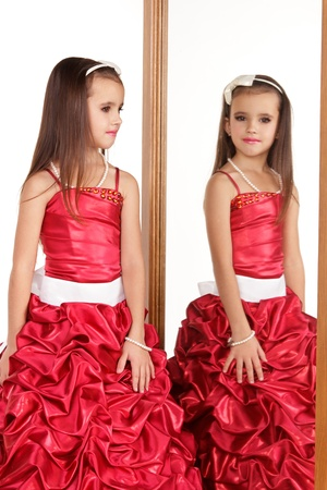 red evening: Beautiful little girl in red evening dress in front of mirrow on white background